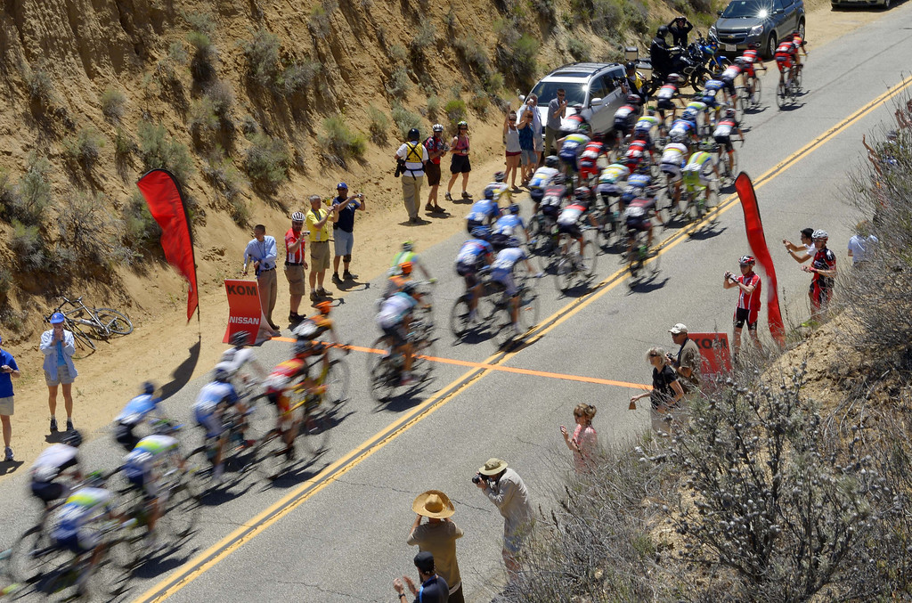 . The peloton goes by fans during the third stage of the Tour of California cycling race, Tuesday, May 14, 2013, near Santa Clarita, Calif.  (AP Photo/Mark J. Terrill)