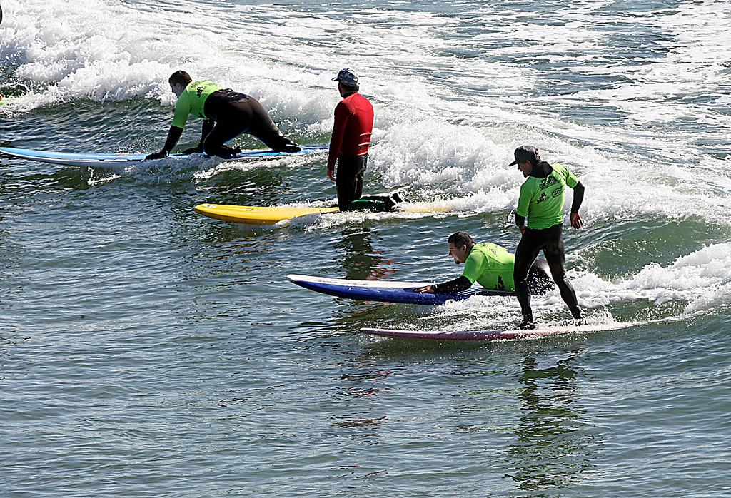 . Rehabbing wounded soldiers Ryan Hawk and Craig Andrade ride the same wave at Cowell surf break in Santa Cruz, Calif., Tuesday, April 16, 2013.  (Dan Coyro/Sentinel)