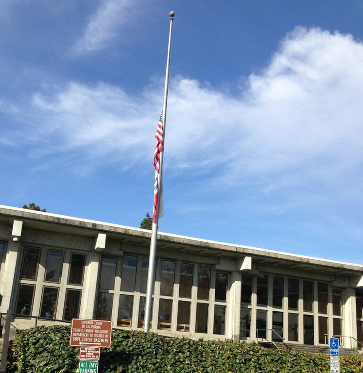 . The flags were at half-staff outside Santa Cruz County Superior Court on Wednesday following the fatal shootout that killed two police officers and one suspect Tuesday. (Jessica M. Pasko/Sentinel)