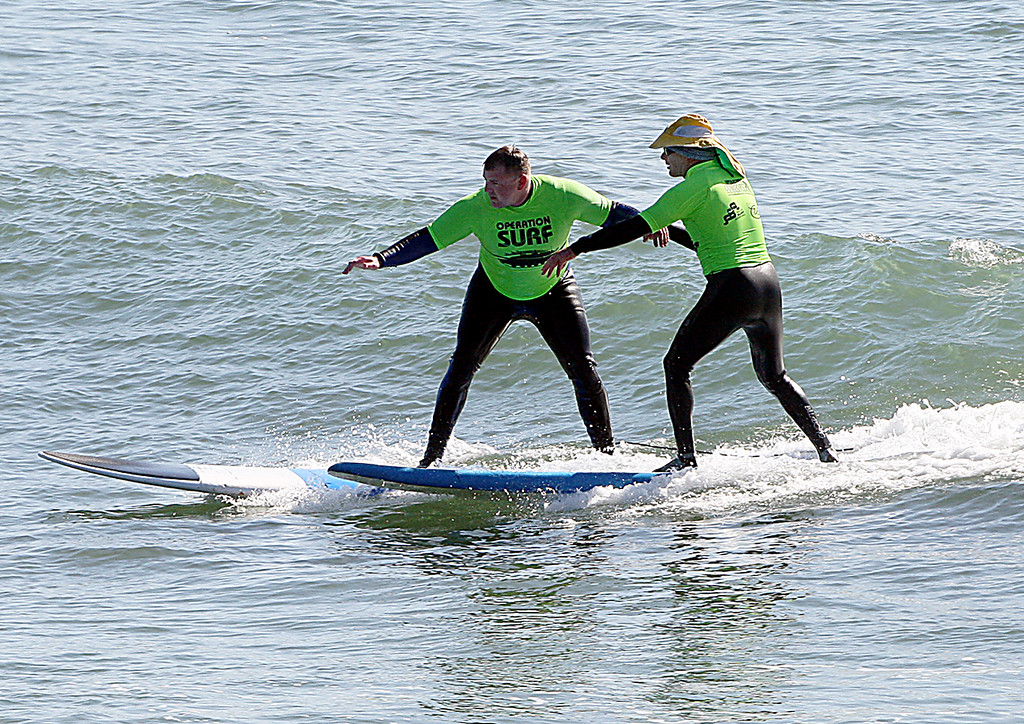 . Santa Cruz surf instructor Richard Schmidt, at right, steadies a wouknded soldier as he stands up on a wave at Cowell surf break in Santa Cruz, Calif., on Tuesday, April 16, 2013.  (Dan Coyro/Sentinel)