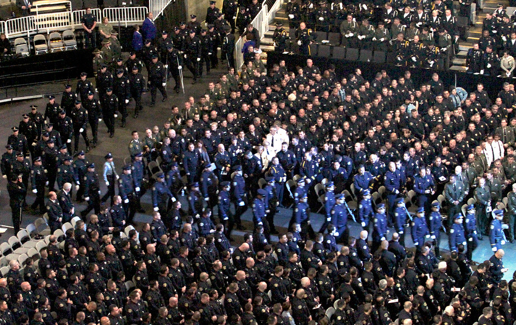 . Members of the Santa Cruz Police Department march in formation as they enter the memorial service for detective Loran \'Butch\' Baker and Elizabeth Butler on Thursday at HP Pavilion. (Shmuel Thaler/Sentinel)