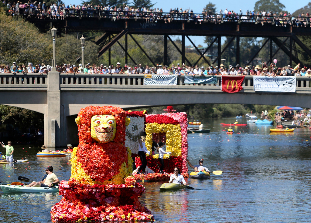 . An elaborate lion float with a moving head makes its way underneath the Soquel Creek bridge in Capitola Village on Sunday afternoon during the annual Begonia Festival Nautical Parade. (Kevin Johnson -- Santa Cruz Sentinel)