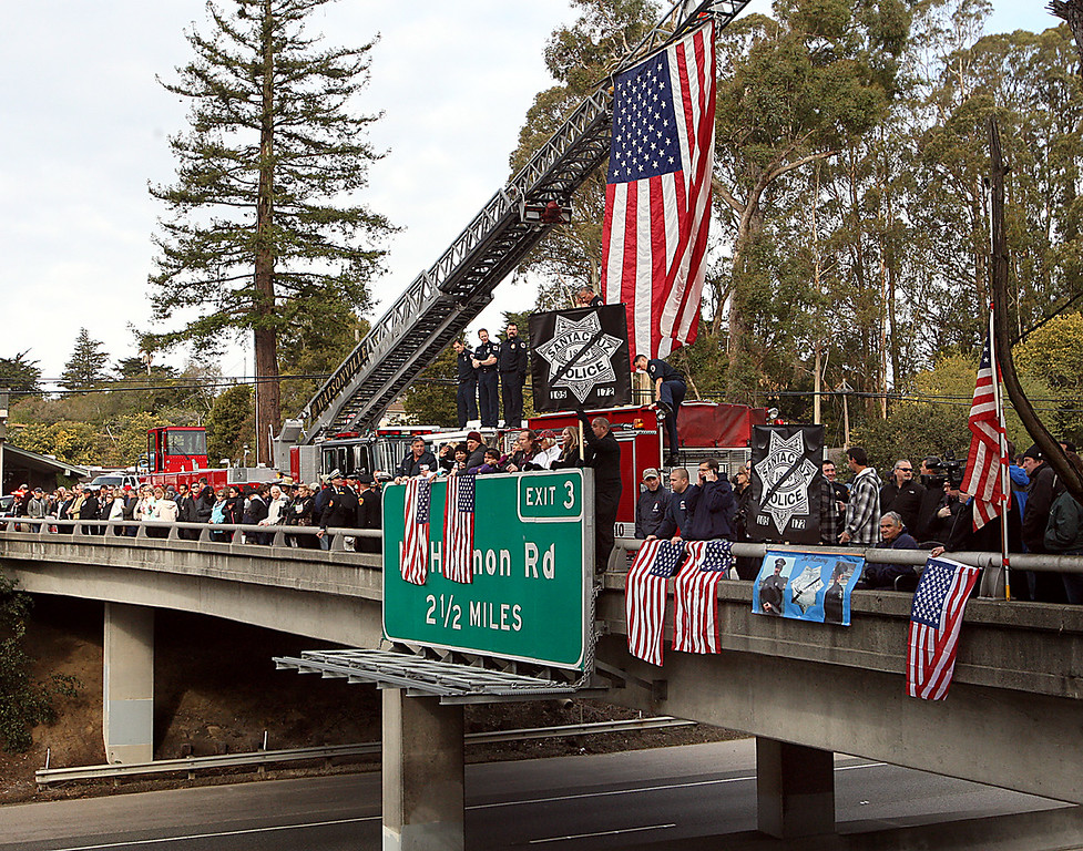 ". Santa Cruz residents join firefighters on the Pasatiempo Highway 17 overpass Thursday to pay their respects to the passing funeral procession that\'s en route to HP Pavilion in San Jose, Calif., for the memorial services for slain Santa Cruz Police detectives Sgt. Loran \'Butch\' Baker and Elizabeth Butler. For more coverage, please visit <a href=""http://www.santacruzsentinel.com\"">www.santacruzsentinel.com</a>. (Dan Coyro/Sentinel)"