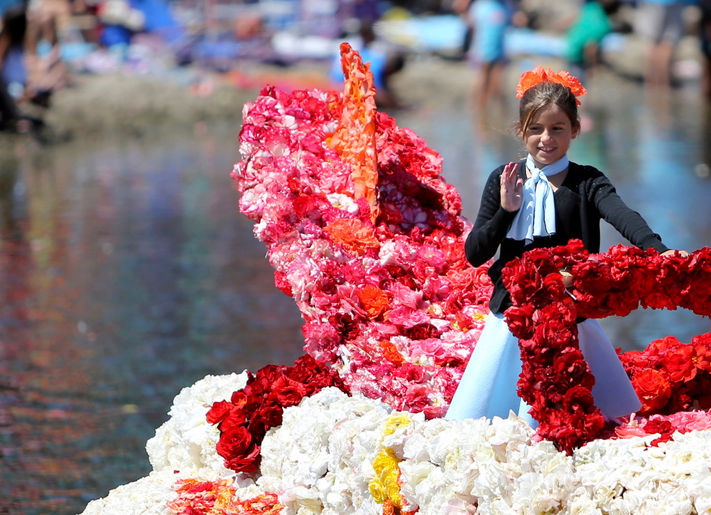 . A young parade participant waves to the crowds on Capitola Beach along Soquel Creek on Sunday during the annual Begonia Festival Nautical Parade. (Kevin Johnson -- Santa Cruz Sentinel)