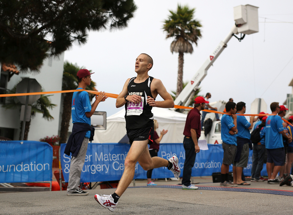 . A runner slows to a halt after crossing the Wharf to Wharf finish line in Capitola on Sunday. (Kevin Johnson -- Santa Cruz Sentinel)